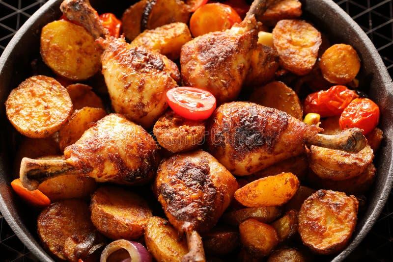 Piernas de pollo asadas con la patata cocida en el sartén fotografía de archivo