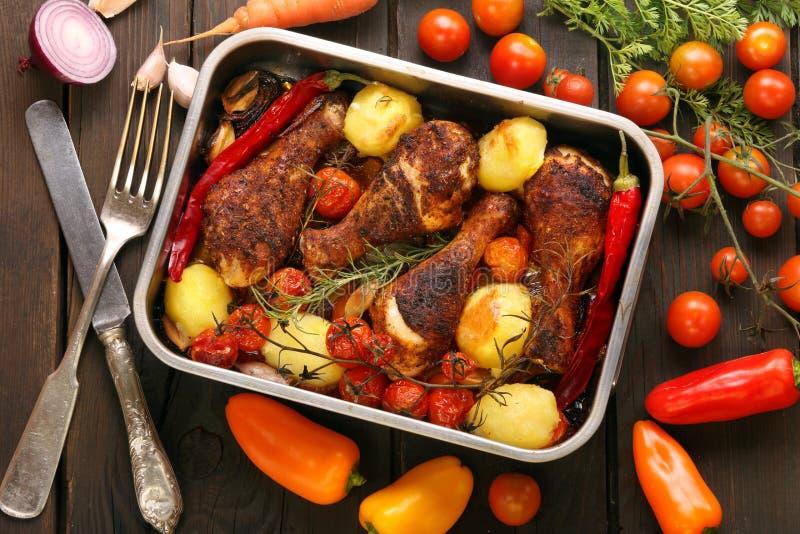 Piernas de pollo asadas con las patatas y las verduras en la cacerola foto de archivo libre de regalías