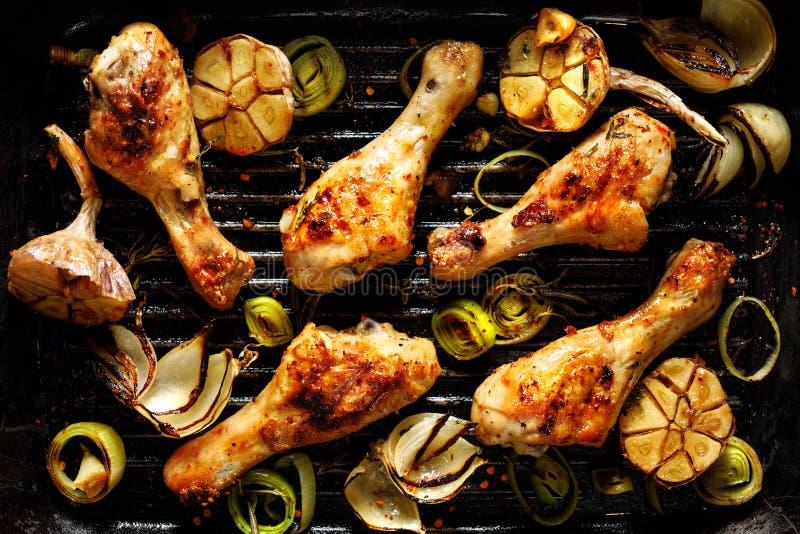 Piernas de pollo asadas a la parrilla con las hierbas y las verduras aromáticas en una placa de la barbacoa imágenes de archivo libres de regalías