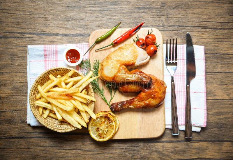 Piernas de pollo asadas a la parrilla en el tablero de madera de la placa con los chiles del limón de los tomates de la salsa de  imagen de archivo libre de regalías