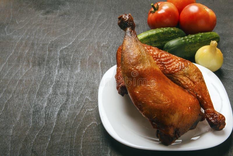 Piernas de pollo de aves de corral, cocinadas en una parrilla en una placa blanca Verduras orgánicas frescas en un fondo negro Co imágenes de archivo libres de regalías