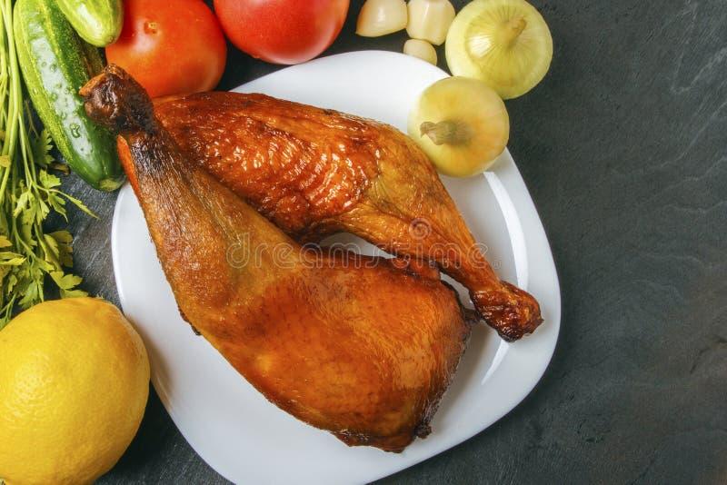 Piernas de pollo de aves de corral, cocinadas en una parrilla y verduras orgánicas en un fondo de madera negro Visión superior Co imagen de archivo