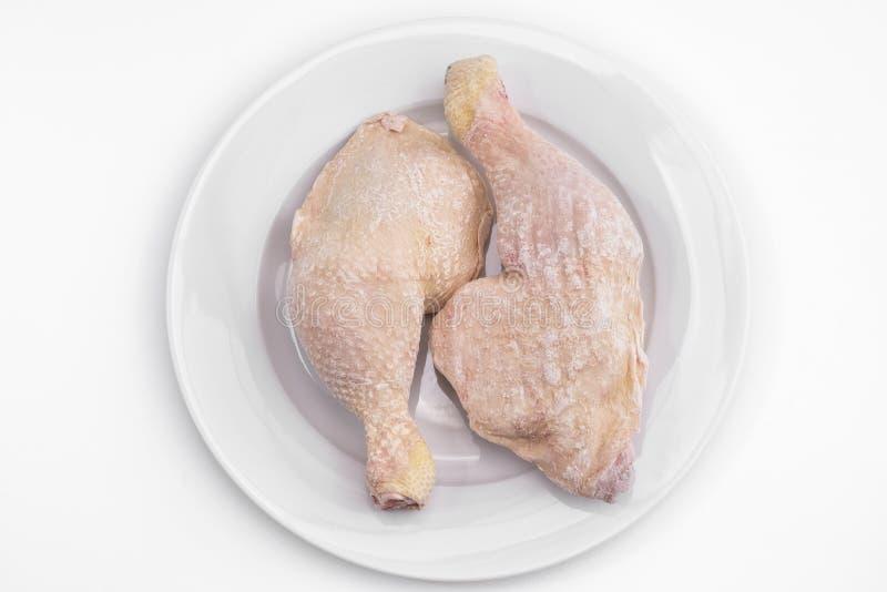 Piernas de pollo congeladas en una placa foto de archivo libre de regalías