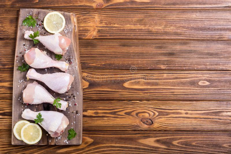 Piernas de pollo crudas con las especias y el perejil fotos de archivo