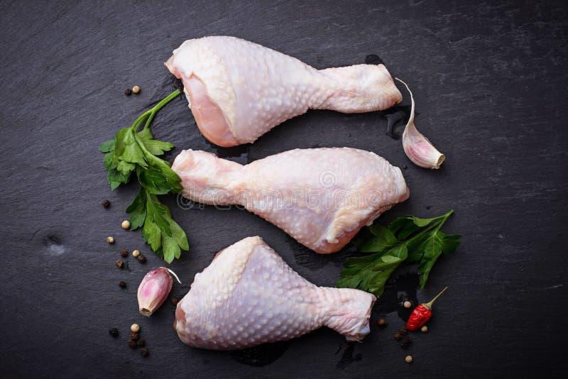 Piernas de pollo crudas con perejil fotos de archivo