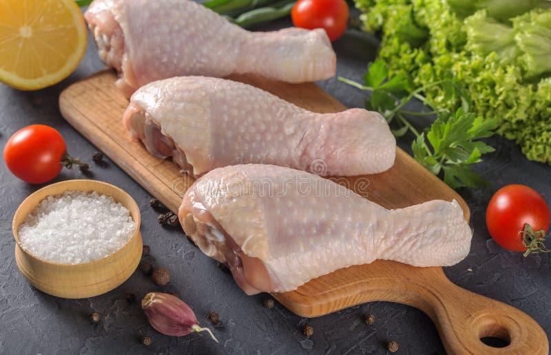 Piernas de pollo crudas con perejil del limón de los tomates en una tabla de cortar foto de archivo libre de regalías