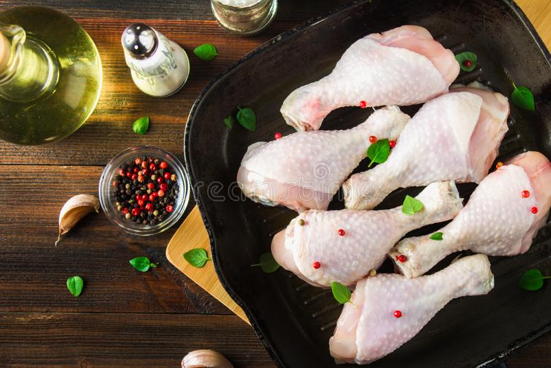 Piernas de pollo crudas en un sartén en una tabla de madera Ingredientes de la carne para cocinar Visión superior fotos de archivo