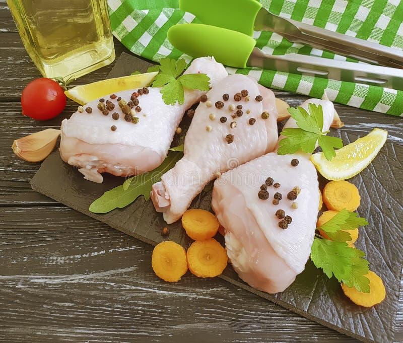 Piernas de pollo crudas, ingrediente del perejil, fondo de madera de las especias de la frescura de la receta del tablero culinar fotografía de archivo