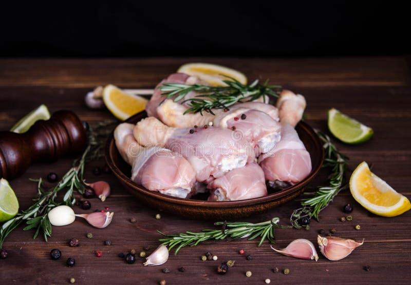 Piernas de pollo crudas, palillos en la placa, carne con las especias para cocinar foto de archivo libre de regalías