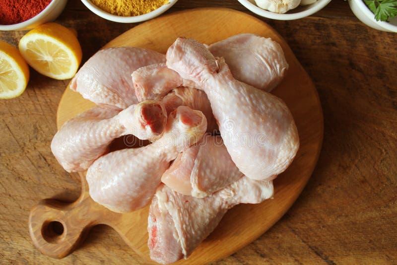 Piernas de pollo crudas crudas, palillos en la tabla de cortar, carne con los ingredientes para cocinar fotografía de archivo