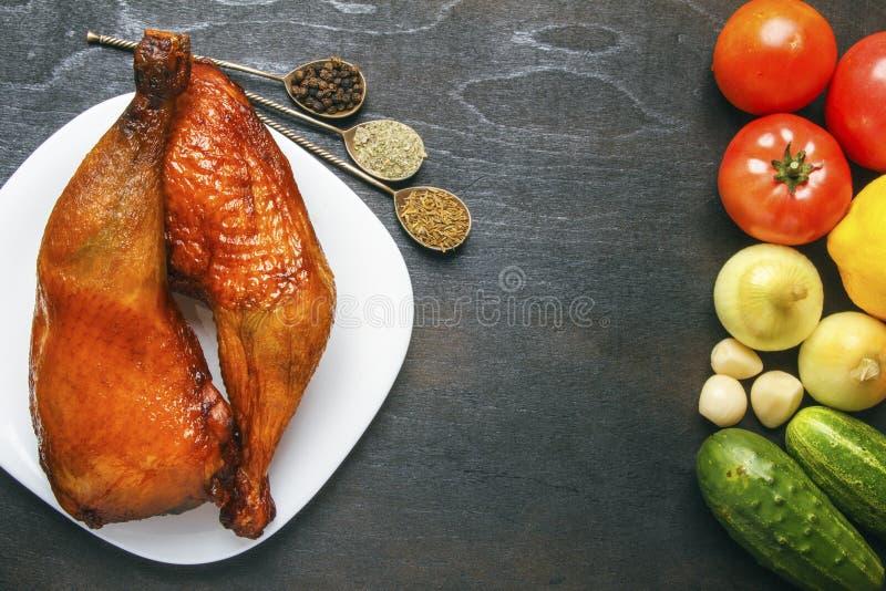 Piernas de pollo curruscantes con las verduras y las especias orgánicas en fondo de madera negro de la tabla Visión superior desd imagenes de archivo