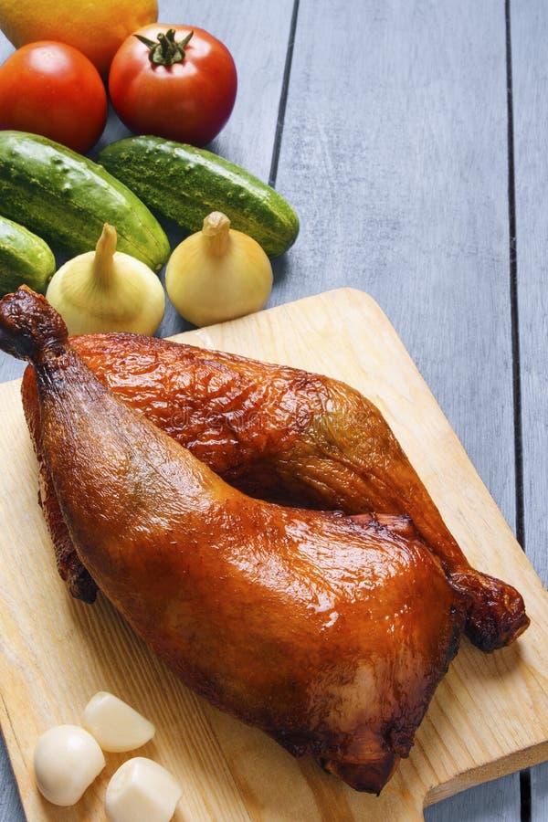 Piernas de pollo curruscantes en tabla de cortar Verduras y especias orgánicas en fondo de madera de la tabla vertical Copie el e fotos de archivo