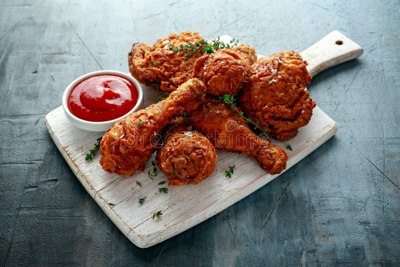 Piernas de pollo curruscantes fritas, muslo en la tabla de cortar blanca con la salsa de tomate e hierbas fotografía de archivo libre de regalías