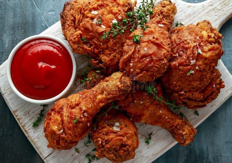 Piernas de pollo curruscantes fritas, muslo en la tabla de cortar blanca con la salsa de tomate e hierbas foto de archivo libre de regalías
