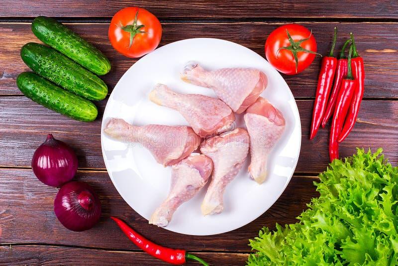 Piernas de pollo frescas, verdes, verduras imagenes de archivo