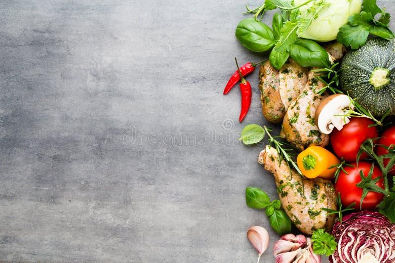 Piernas de pollo picantes, verduras frescas en un fondo gris top VI fotografía de archivo libre de regalías