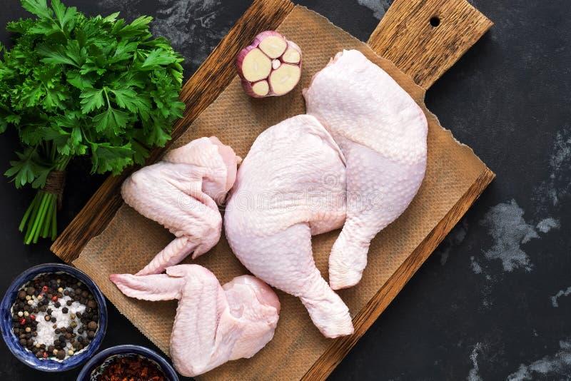 Piernas de pollo y alas crudas en un tablero de madera, ajo, perejil, especias Fondo rural, endecha plana imágenes de archivo libres de regalías