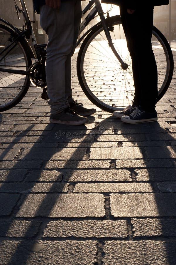 Piernas de un par joven cara a cara con la bicicleta fotos de archivo libres de regalías