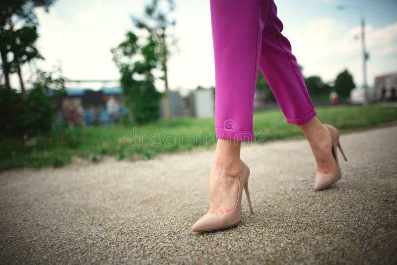 piernas de una chica joven en talones en paso en fondo de la hierba imagen de archivo libre de regalías