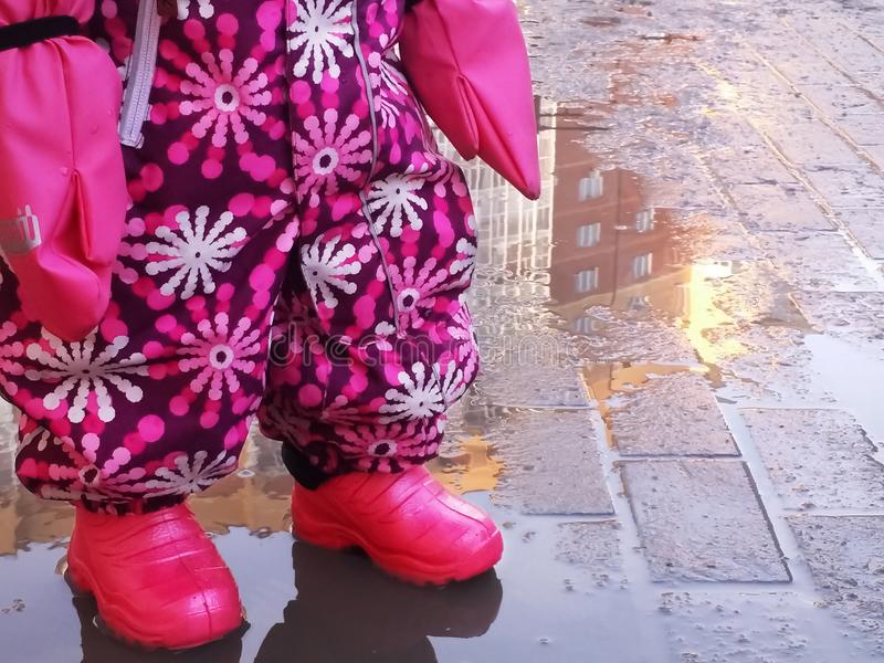 Piernas del bebé en chanclos, guardapolvo y la pieza rosados de manos en guantes fotos de archivo libres de regalías
