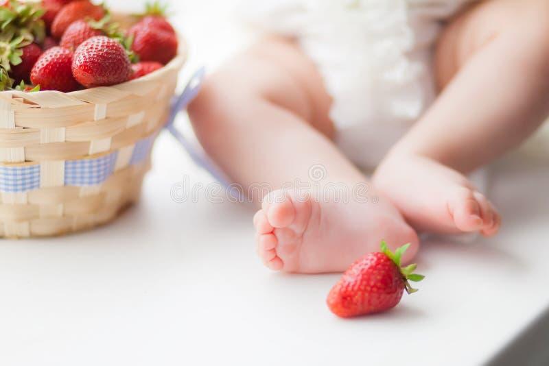 Piernas del bebé en un fondo blanco al lado de una cesta de fresas, humor de la baya imagen de archivo libre de regalías