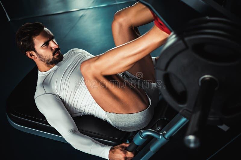 Piernas del entrenamiento del hombre en la máquina de la prensa de la pierna foto de archivo
