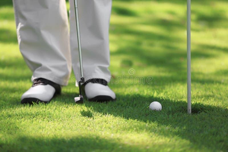 Piernas del hombre joven que juegan a golf en curso imagen de archivo