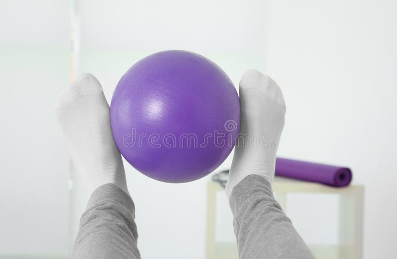 Piernas del hombre que hacen ejercicios con la bola de goma imagen de archivo