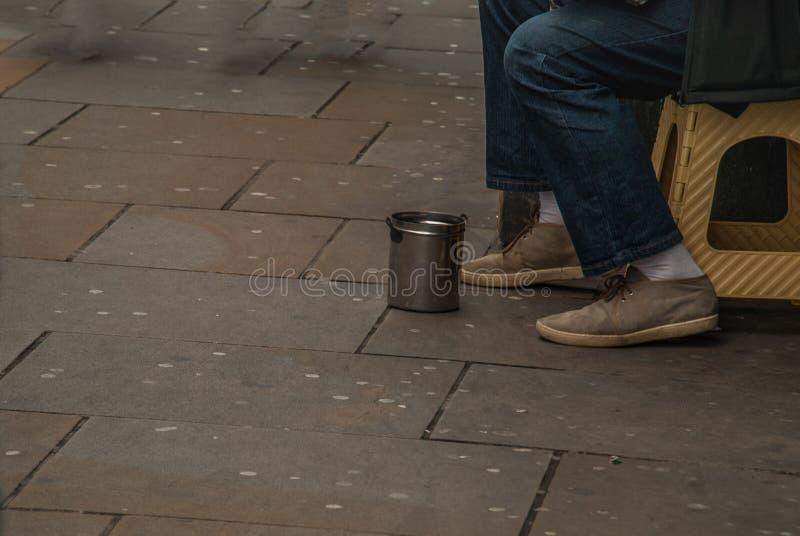 Piernas del mendigo o del hombre sin hogar, mendigos en las calles de la ciudad fotos de archivo