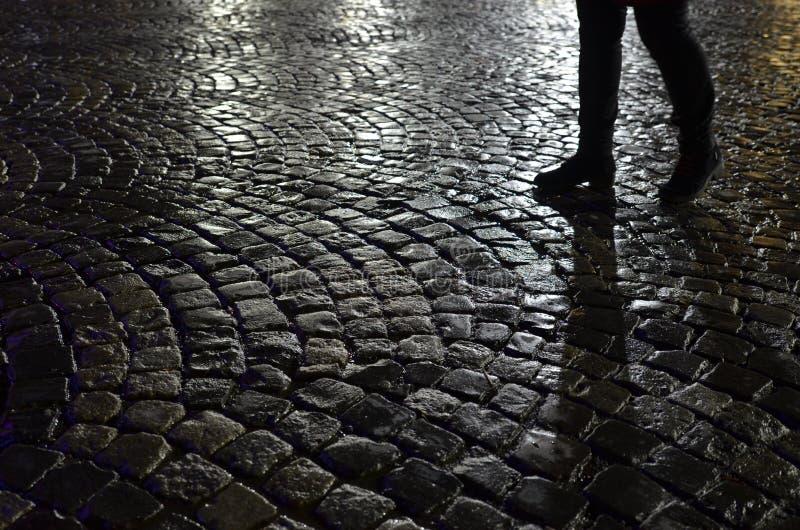 Piernas del ` s de la mujer en el guijarro mojado en la noche fotografía de archivo