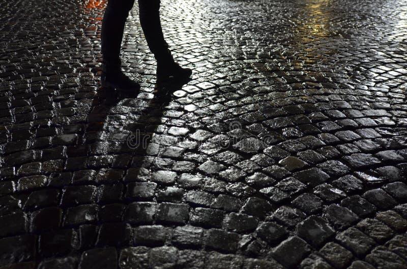 Piernas del ` s de la mujer en el guijarro mojado en la noche foto de archivo