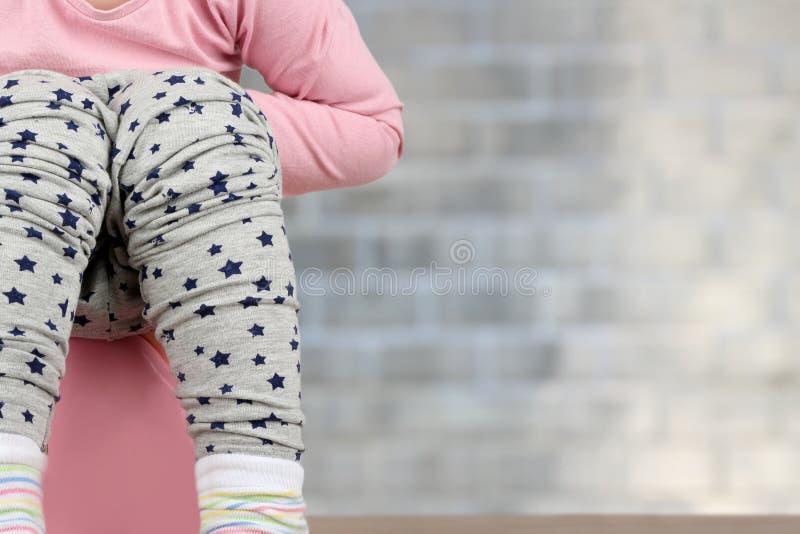 Piernas del ` s de los niños que cuelgan abajo de un cámara-pote en un fondo azul fotografía de archivo libre de regalías