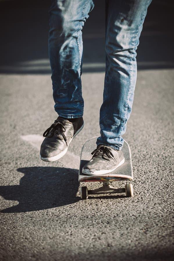 Piernas del skater que montan el monopatín en la calle fotografía de archivo libre de regalías