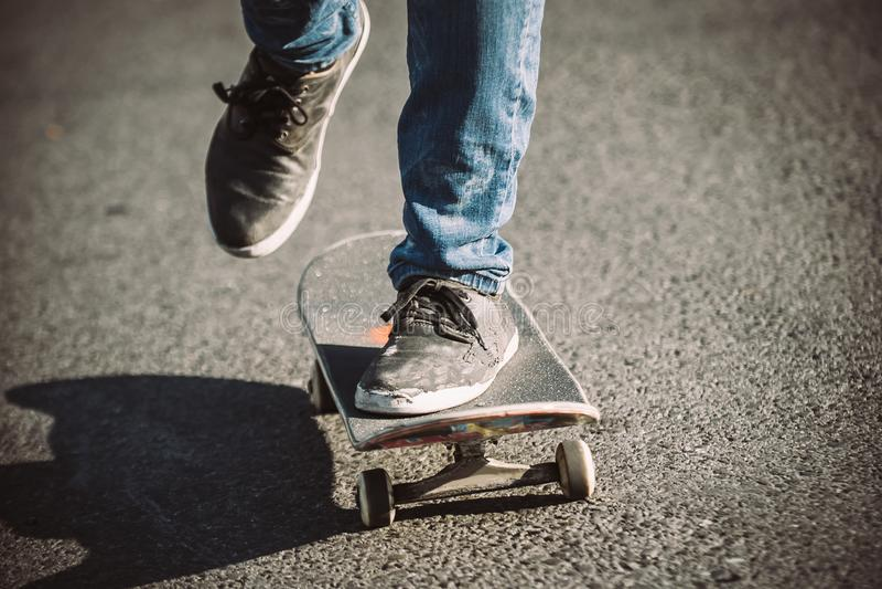 Piernas del skater que montan el monopatín en la calle imagen de archivo libre de regalías