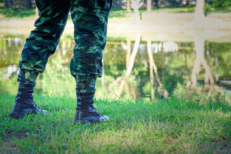 Piernas del soldado que colocan el río cercano, cierre encima de la visión, botas negras fotografía de archivo