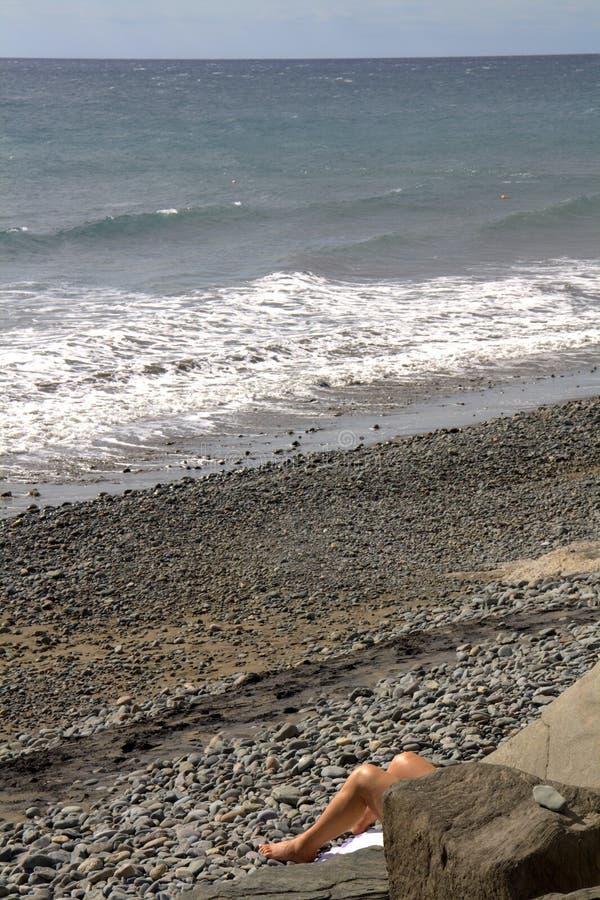 Piernas del sunbather en la playa imagen de archivo