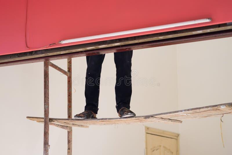 Piernas del trabajador en escalera frágil fácil Concepto de trabajador de la pintura y de trabajo peligroso fotos de archivo libres de regalías