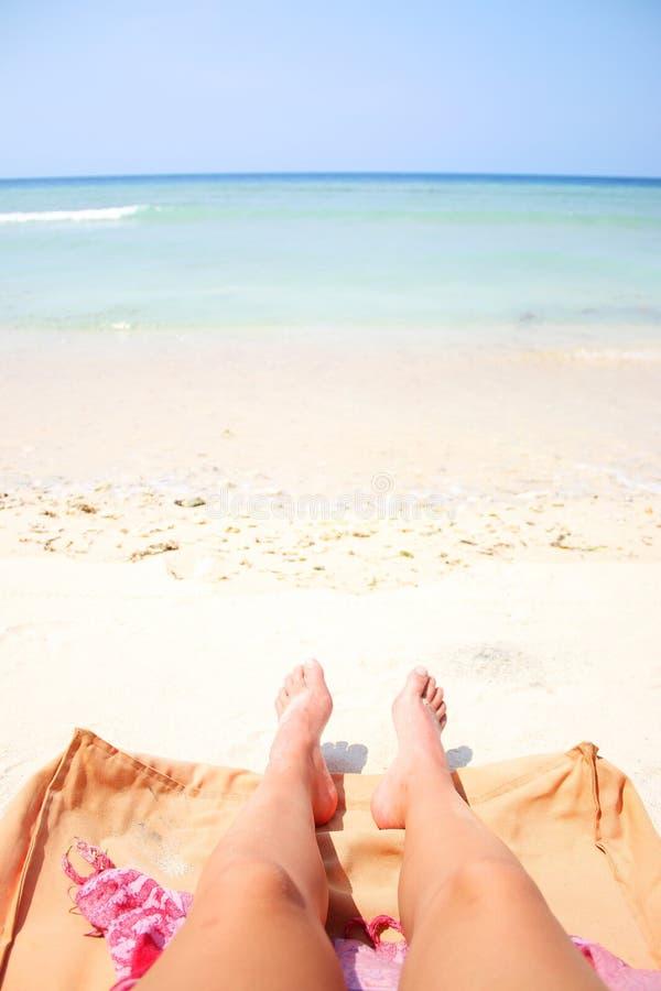 Piernas del verano en la playa fotografía de archivo
