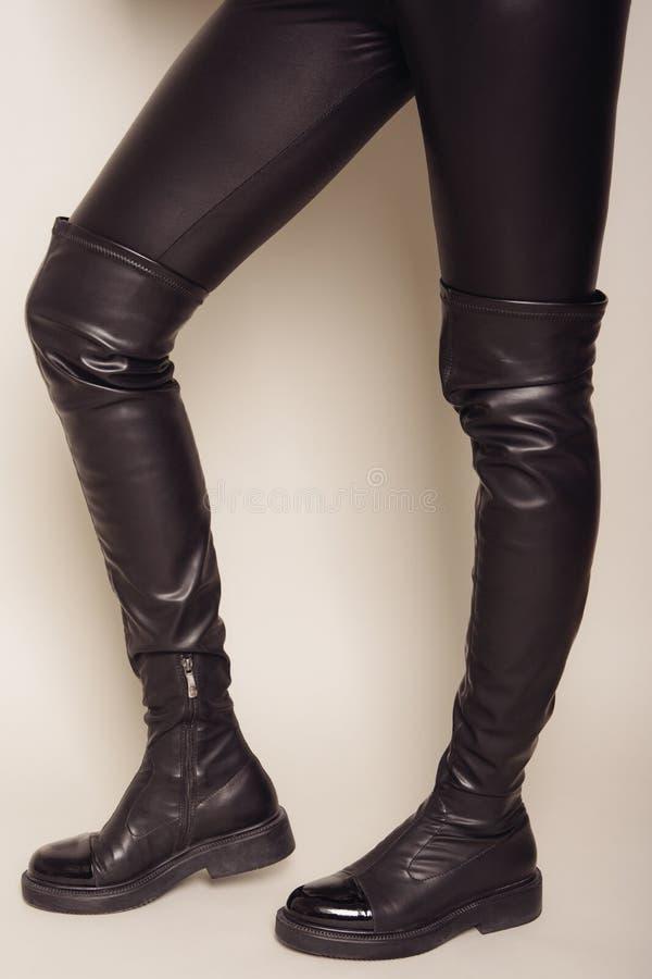 Piernas delgadas del ` s de las mujeres en pantalones de cuero negros y altas botas elegantes foto de archivo