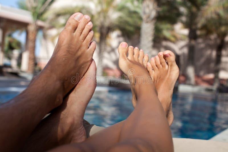 Piernas descalzas de los pares del primer en el centro turístico foto de archivo libre de regalías