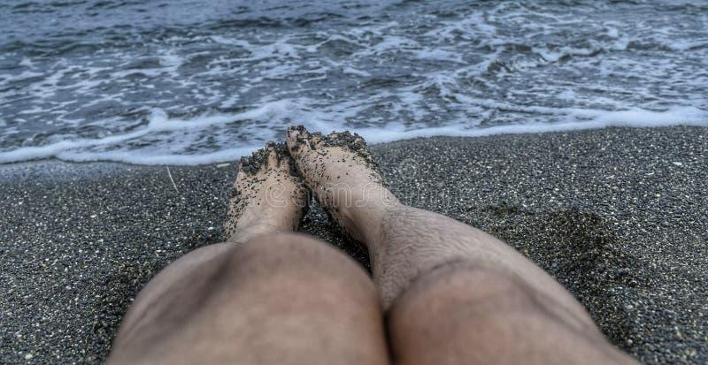 Piernas en arena, el mar, y ondas negros fotos de archivo libres de regalías