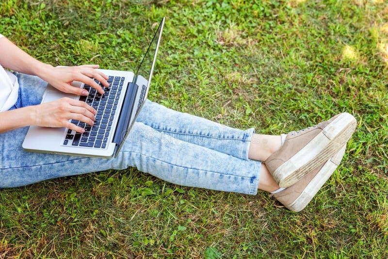 Piernas en césped de la hierba verde en parque de la ciudad, manos de la mujer que trabajan en el ordenador de la PC del ordenado fotos de archivo