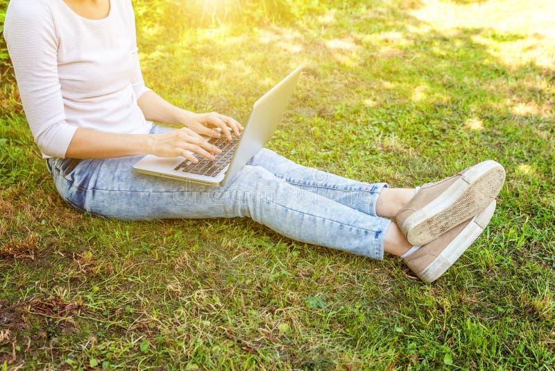Piernas en c?sped de la hierba verde en parque de la ciudad, manos de la mujer que trabajan en el ordenador de la PC del ordenado imagenes de archivo