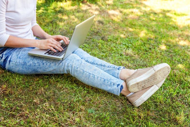 Piernas en c?sped de la hierba verde en parque de la ciudad, manos de la mujer que trabajan en el ordenador de la PC del ordenado fotografía de archivo