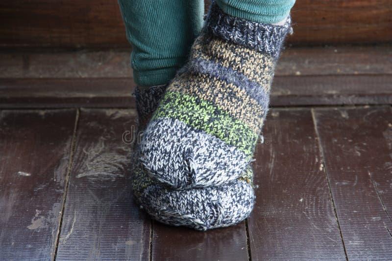 Piernas en calcetines hechos punto como s?mbolo de la vida en el campo fotos de archivo
