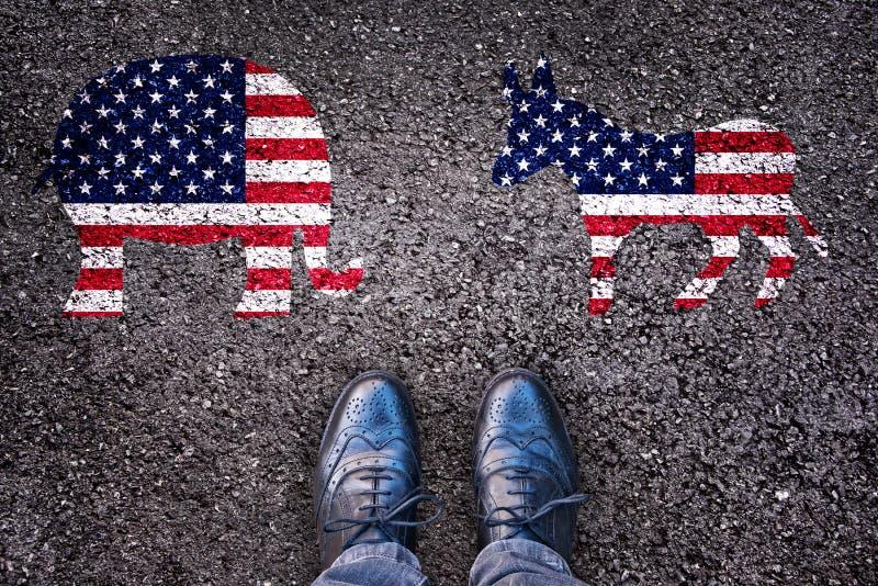 Piernas en la carretera de asfalto con el elefante y el burro, elección americana imagen de archivo