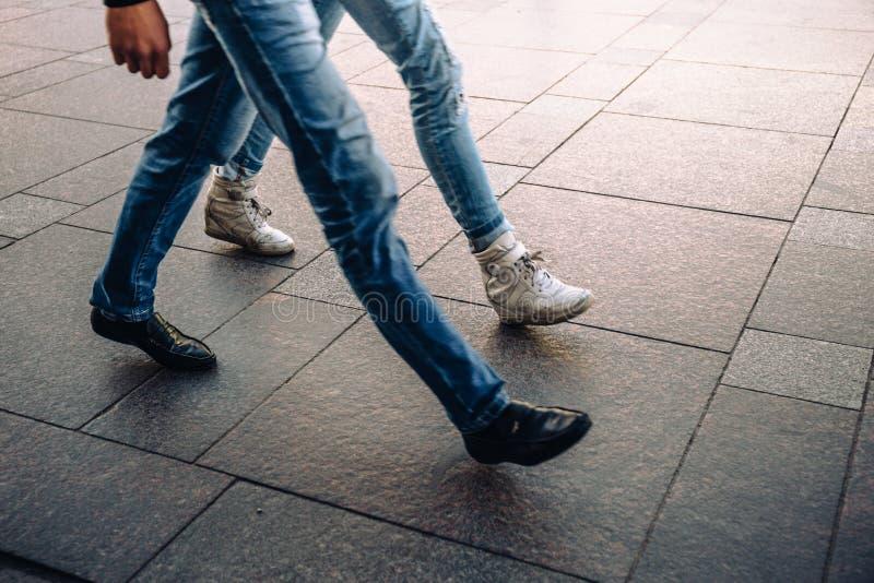 Piernas en vaqueros del hombre joven y de la mujer en zapatos de la calle que caminan o que van rápidamente imágenes de archivo libres de regalías