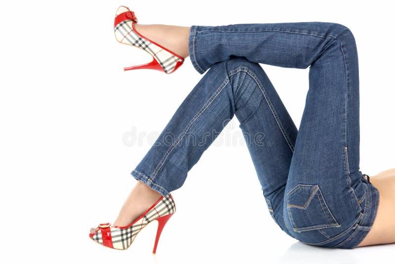 Piernas femeninas de mentira en pantalones vaqueros fotografía de archivo