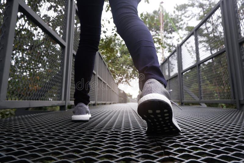Piernas femeninas delgadas en los tejanos y las zapatillas de deporte grises que caminan a lo largo de rastro del bosque imágenes de archivo libres de regalías