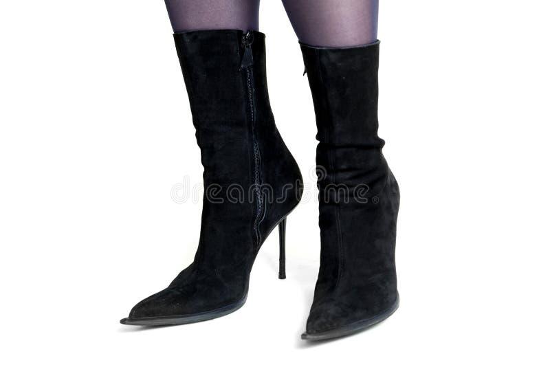 Piernas femeninas delgadas en vista lateral de las botas negras del ante imágenes de archivo libres de regalías